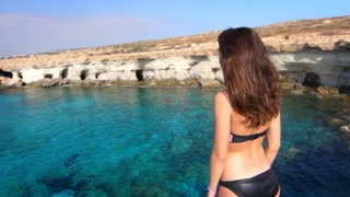 Brunette woman with arms outstretched enjoying sea view. Tourist woman enjoy sea landscape. Back side of pretty girl looking at sea in slow motion. Summer vacation in Cyprus. Sea relax concept