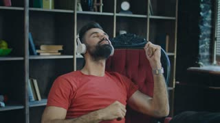 Business man dancing in chair in office. Young man listening to music in headphones and dancing at workplace. Beard man listening to music at work and dance in chair
