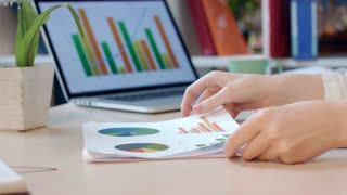 Business woman analyzing financial diagrams at office. Female hands holding finance report at office table. Woman analyzing business documents at office workplace. Business papers analysis concept