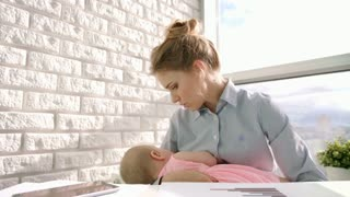 Business woman care baby at home. Worried mother holding baby on hands. Little infant girl sleeping in mother embrace. Working mom with child at office. Mother carrying sleeping kid