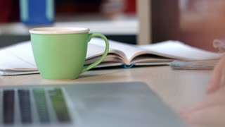 Business woman drink coffee in office. Close up of woman hand holding green coffee cup on desk. Corporate business office lifestyle. Coffee break and relaxing on workplace. Female hand hold cup of tea