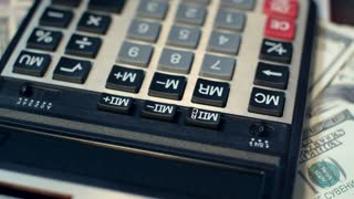 Business woman hand using calculator at office. Close up of financial adviser working with calculator. Business accounting calculating money profit. Calculator on background of dollar banknotes
