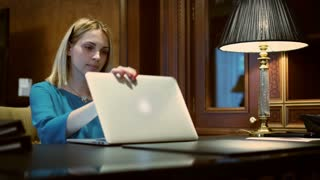 Business woman opening notebook computer for working on desk with table lamp. Young woman using notebook in luxury interior home office
