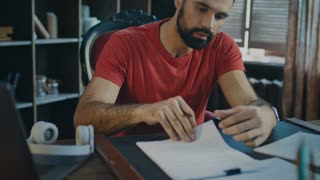 Businessman signing last contract in end of day and throwing papers to desk. Man tired from paperwork. Young business man working with documents in home office