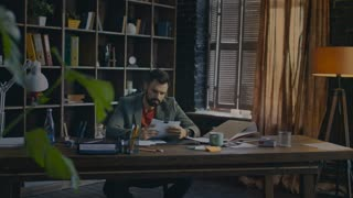 Businessman working with paper documents. Business man working with business contract at table in cozy home office. Home business work. Business owner attentive for details of contract