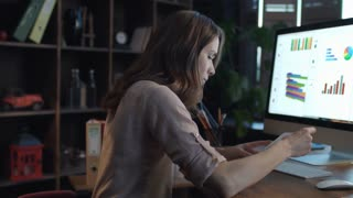 Businesswoman analyzing market statistics. Young woman business analyst using computer to generate financial report in office. Female marketer thinking marketing strategy