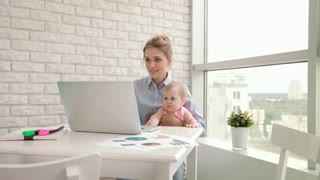 Businesswoman with kid on hands working with documents. Beautiful mother working on laptop with child girl in cozy home. Freelancer at maternity leave. Busy mother with infant thinking about work