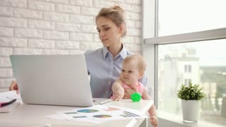 Busy woman with baby not concentrated at work. Mother working on laptop with child on hands. Business mother looking documents with kid at cozy home. Multitasking woman employee