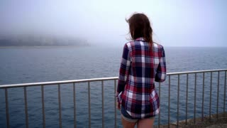 Calm woman back looking sea. Young woman coming to edge of embankment. Girl looking away on bank of fog sea. Back view of woman looking on fog ocean