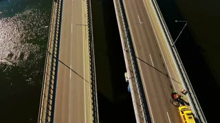 Car bridge over river. Drone view of highway bridge above river. Cars and truck driving along highway bridge. Highway road on river landscape. Cars moving on road aerial view