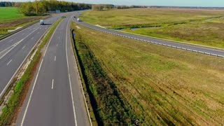 Cars and truck moving on road junction. Drone view of highway road. Sky view of cars traffic at highway road in field. Aerial view cars driving on highway. Cars moving on asphalt road