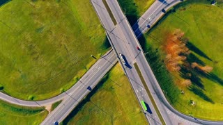 Cars driving on highway intersection. Highway junctions. Aerial view of cars moving on highway interchange. Drone view of cars traffic on circle road. Interchange highway road. Round road aerial view