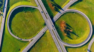 Cars moving on highway interchange. Aerial view of intersection highway. Road junctions. Cars traffic on circle road view from above. Interchange highway road. Aerial view of circle road aerial view