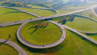 Cars moving on road interchange. Cars traffic on highway intersection. Winding road aerial. Aerial view highway junction. Highway crossing. Aerial view circle road