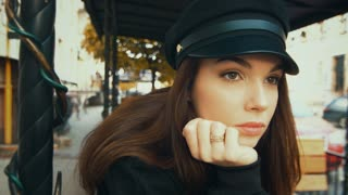 Charming fashion model in black cap. Portrait of glamorous young woman relaxing outdoors. Close up face of elegant woman with beautiful eyes. Fashionable girl posing in urban landscape at daylight