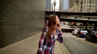 Cheerful woman talking phone and smiling. Young smiling woman talking on mobile phone in modern city and looking away. Mobile phone conversation. Brunette woman talking phone in street urban
