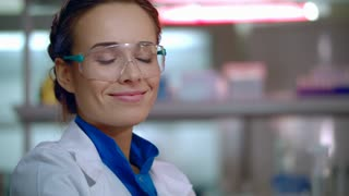 Chemist woman smiling. Close up of female chemist face in safety glasses. Smiling woman chemist in lab. Happy chemist scientist portrait. Smiling scientist in science lab