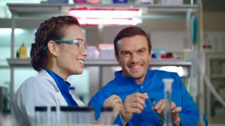 Chemistry scientist have fun at work. Chemistry research teamwork. Chemical researchers smiling in laboratory. Female and male scientists working in research lab. Scientists in lab