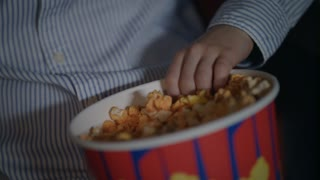 Child hand taking popcorn from paper box at cinema. Close up of kids hands take pop corn flakes from bowl at movie theater