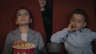 Children eat popcorn in cinema. Preschool children watching movie in cinema. Boy taking popcorn from box in movie theatre. Kids eating popcorn in movie theater. Movie entertainment industry