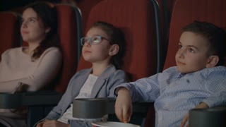 Children got scared in cinema. Kids are frightened at movie theatre. Scared children cover faces by hands. Kids watching horror film. Scary movie concept