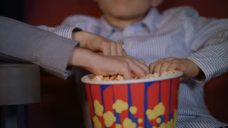 Children hands taking popcorn from paper box. Close up of child hands taking popcorn from bowl. Children eating popcorn from one box at cinema. Cinema food for kids