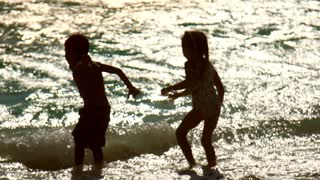 Children have fun at sunset waves. Boy and girl silhouettes enjoy summer waves in slow motion. Happy kids enjoy water waves at sunset beach