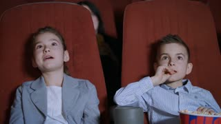 Children laughing at cartoon cinema. Kids laughing in cinema. Boy and girl watching funny movie. Smiling child watching cartoon in movie theatre. Little spectators at cinema hall