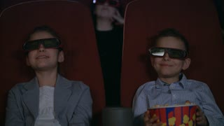 Children talking in cinema. Children share their impressions of 3D film. Boy and girl watch 3d film in slow motion. Beauty children in 3D glasses watching movie with interest. Kids movie entertainment