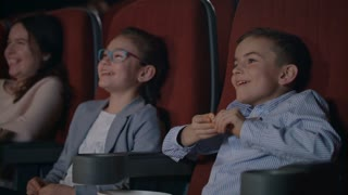 Children watching movie enthusiastically in cinema. Happy boy and girl watching comedy film at cinema. Girl coughing in cinema. Young spectators enjoy fun cartoon. Child entertainment concept