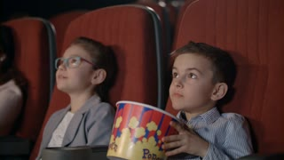 Children watching movie in cinema. Boy eating popcorn from paper box. Boy and girl watching cartoon film at movie theatre. Movie entertainment for kids