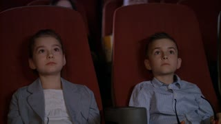 Children wearing 3d glasses at cinema chair. Brother and sister watching 3d film together in slow motion. Boy and girl watching 3d cartoon at movie theater. Modern movie entertainment for kids