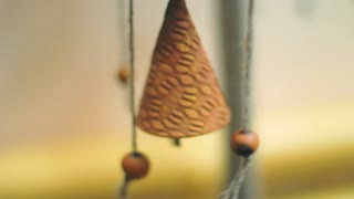 Chinese bells hanged indoors. Close up of antique Feng shui amulet for luck and protection. Wind swinging clay bells slowly. Feng shui chimes