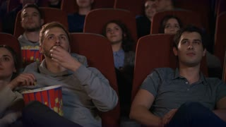 Cinema audience eating popcorn and watching movie. Loving couple embracing in cinema. Cinema friends enjoy film. Couple eating pop corn in slow motion