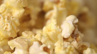 Cinema popcorn background. Ready popcorn flakes falling into heap in slow motion at popcorn machine. Close up of popcorn ready for movie. Process of pop corn production.