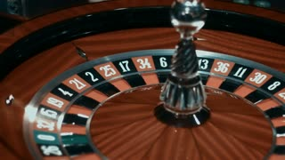 Classic casino roulette on gambling table. Traditional game of chance. Close up wooden roulette wheel slowly rotating. European gambling game in luxury casino
