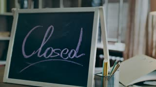 Close sign on board. Sign closed written with chalk on blackboard standing on wooden table in dark creative business studio. Working day is over. Business closed