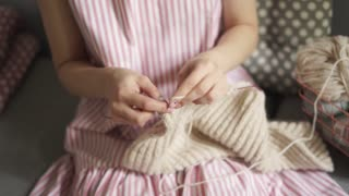 Close up female knitting hands. Woman hobby knitting wool sitting on couch. Woman leisure in home