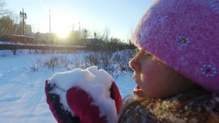 Close up of little girl blowing snow from hands. Kid playing with snow in slow motion. Winter wonderland. Portrait of winter girl holding snow
