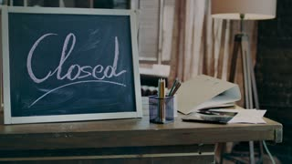 Close up of sign closed written with chalk on blackboard standing on table with organizer and pencils in dark office. Today office closed. Business closed sign