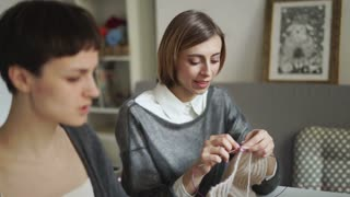 Close up of two woman face knitting thread in creative studio. Young woman knitting wool texture together friend in home