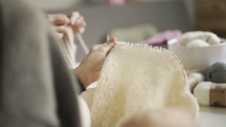 Close up of woman knitting hands. Female hands knitting needles white wool fabric from wool yarn. Woman hobby