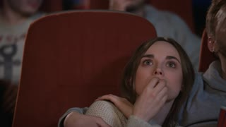 Close up of young people faces watching movie at cinema theater. Love couple people eating popcorn at cinema theatre in slow motion