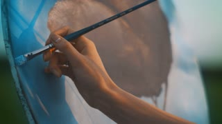 Close up woman hand with paintbrush painting on canvas. Professional painter at work. Woman hand oil painting outdoor