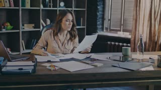 Concentrated businesswoman reading schedules on paper. Woman analyzing business documents at office. Marketer thinking about marketing strategy. Female employee working with papers with market graph