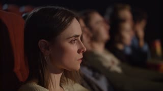 Concentrated girl watching thrilling movie at cinema. Young woman watching movie in movie theater. Pretty girl watching exciting movie in cinema. Enjoy cinema concept