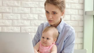 Concentrated woman with baby on hands working on laptop. Serious business woman with child working notebook. Young mother with kid looking laptop at home. Mom with toddler working together