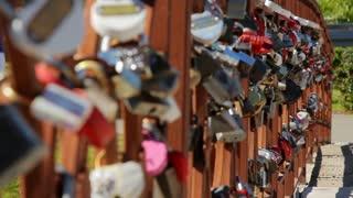 Concrete bridge with multiple love locks on metal railing. Love locks on a fence on bridge at summer park. Set of wedding padlocks on bridge of love