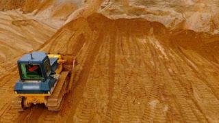 Crawler bulldozer standing at sand mine. Mining bulldozer on sand background. Mining machinery standing at industrial sand quarry. Sand mining process. Earth moving equipment. Construction machinery