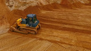 Crawler bulldozer working in sand quarry. Top view of bulldozer mining sand at industrial area. Mining machinery in sand mine. Sand mining industry. Earth mover working. Construction industry